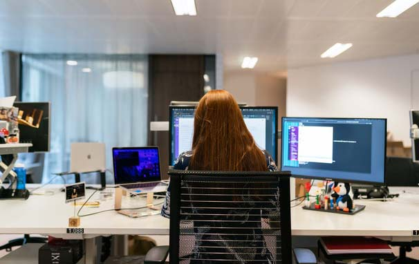 Technology-Enabled woman-sitting-in-front-of-computer-in-office